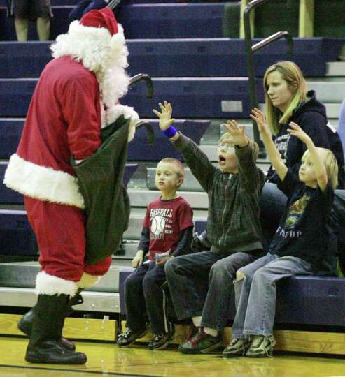 Santa hands out candy to the good boys and girls in the bleachers during a break in the action of th