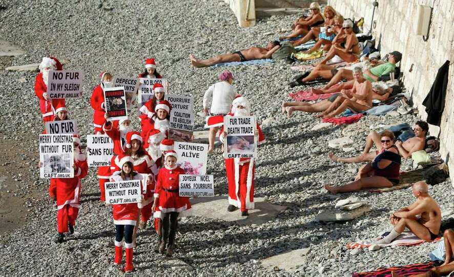 Activists dressed in Santa Claus from the coalition to abolish the fur trade, demonstrate with signs