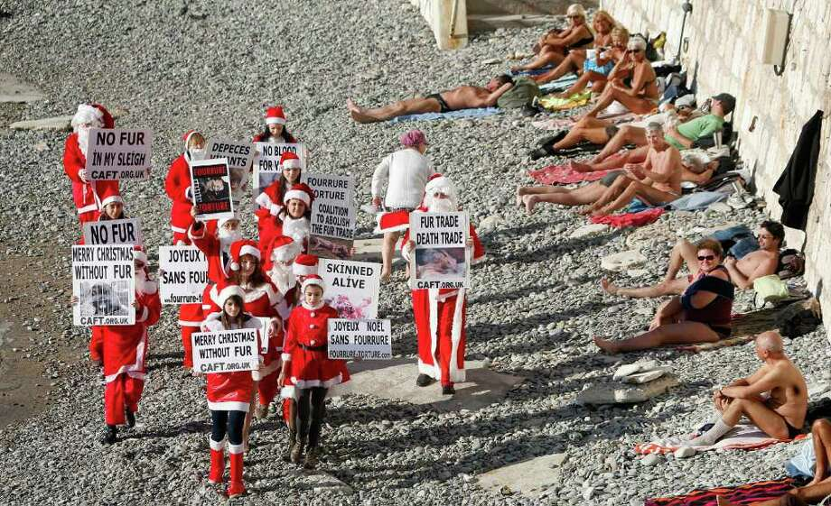 Activists dressed in Santa Claus from the coalition to abolish the fur trade, demonstrate with signs showing animals skinned alive on the beach in Nice, southern France, Saturday, Dec. 17, 2011. Activists exhort shoppers not buy fur for Christmas. Photo: Lionel Cironneau, Associated Press / AP