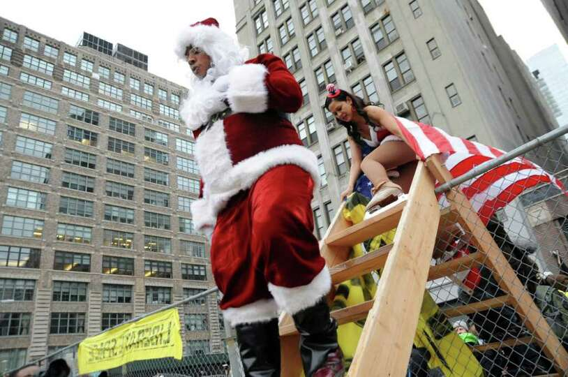 A Protestor dressed as Santa Claus scales a ladder used by members of the Occupy Wall Street movemen