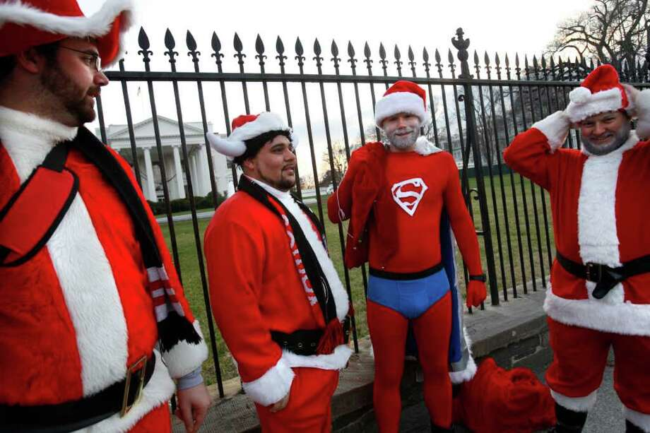 "Ben Owen, left, of Arlington, Va., Jonathan Zapata, of Alexandria, Va., Stuart Gottlieb, of Falls Church, Va. and Mike Terry, of Falls Church, Va., gather outside the White House dressed in Santa suits as they participate in""Santarchy"" in Washington, on Saturday, Dec. 17, 2011. During ""Santarchy,"" an annual holiday event, groups of people wear Santa suits and rove the city. Photo: Jacquelyn Martin, Associated Press / AP"