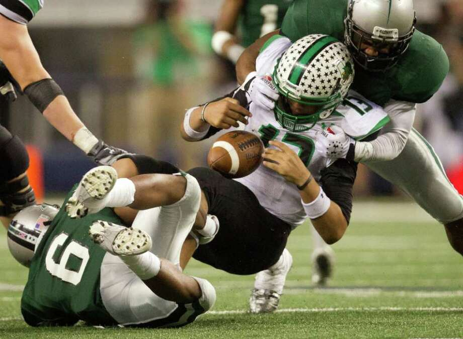 Southlake Carroll quarterback Kenny Hill loses control of the ball, but manages to hold on, as he is hit by two Hightower defenders on the final drive of the game as Carroll runs out the clock on Hightower during the fourth quarter of the 5A Div. 1 state championship high school football game at Cowboys Stadium on Saturday, Dec. 17, 2011, in Arlington.  Southlake Carroll won the game 36-29. Photo: Smiley N. Pool, Houston Chronicle / © 2011  Houston Chronicle