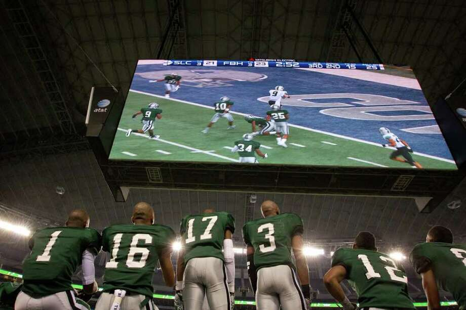 Hightower players watch on the video screen as Southlake Carroll wide receiver Corey Kemp (9) scores on a 20-yard touchdown catch during the second half of the 5A Div. 1 state championship high school football game at Cowboys Stadium on Saturday, Dec. 17, 2011, in Arlington.  Southlake Carroll won the game 36-29. Photo: Smiley N. Pool, Houston Chronicle / © 2011  Houston Chronicle