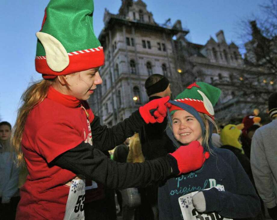 Runners and cousins Olivia Bachmann,12, left, and Tess Fitzmaurice, 9, both of Greenville, ready for the the start of the 15th Annual Last Run 5K  race in Albany Saturday Dec. 17, 2011.    (John Carl D'Annibale / Times Union) Photo: John Carl D'Annibale / 00015785A