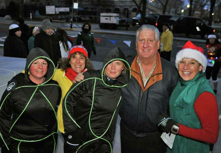 Triathletes (from left) Eachel Knaggs of Troy, Robin Davey of Clifton Park, Jennifer Kendrick of Cohoes and Karen Casper(at far right) of Ballston Lake pose with Albany Mayor Jerry Jennings before the start of the 15th Annual Last Run 5K  race in Albany Saturday Dec. 17, 2011.    (John Carl D'Annibale / Times Union) Photo: John Carl D'Annibale / 00015785A