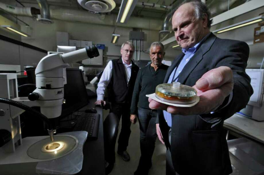 Paul Tolley, CNSE Vice President for Disruptive Technologies and Director of CNSE STC, left, Dr. Alain E. Kaloyeros, Senior Vice President and Chief Executive Officer of the College of Nanoscale Science and Engineering, center, and John P. Willis, Ultradian Diagnostics CEO, talk in a Nanobio lab at Albany NanoTech on Wednesday Dec. 14, 2011, in Albany, N.Y.  Ultradian is working with Albany Nanotech to further develop their products for treating diabetes. Willis holds their current device, which they hope to make much smaller. (Philip Kamrass / Times Union ) Photo: Philip Kamrass / 00015778B