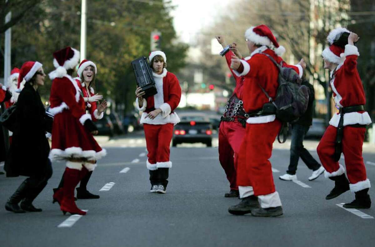 On the walking breaks between pubs, groups of Santas took to the streets, dancing amongst traffic during the annual Santarchy celebration Saturday, Dec. 17, 2011, in Seattle, Wash.