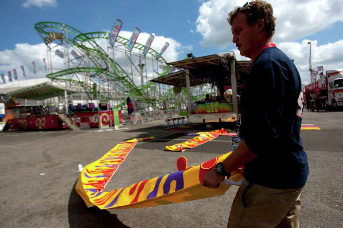 JOHNNY HANSON : HOUSTON CHRONICLE FATAL RIDE: With the Hi Miler roller coaster in the background, Dion Louw, of Ray Cammack Shows, begins to pack up in March. A 47-year-old man died on the ride that month.