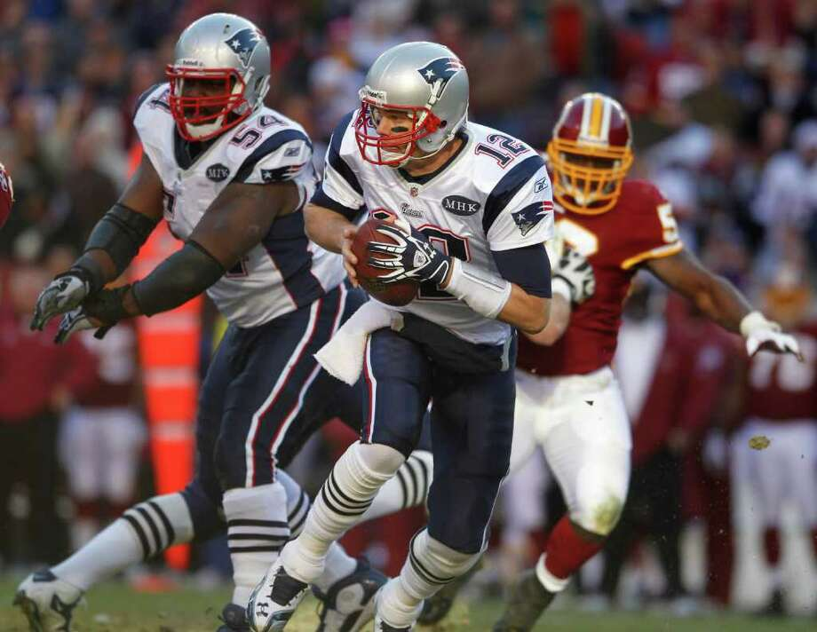 New England Patriots quarterback Tom Brady (12) avoids the Washington Redskins pass rush during the first half of an NFL football game on Sunday, Dec. 11, 2011, in Landover, Md.  (AP Photo/Evan Vucci) Photo: Evan Vucci