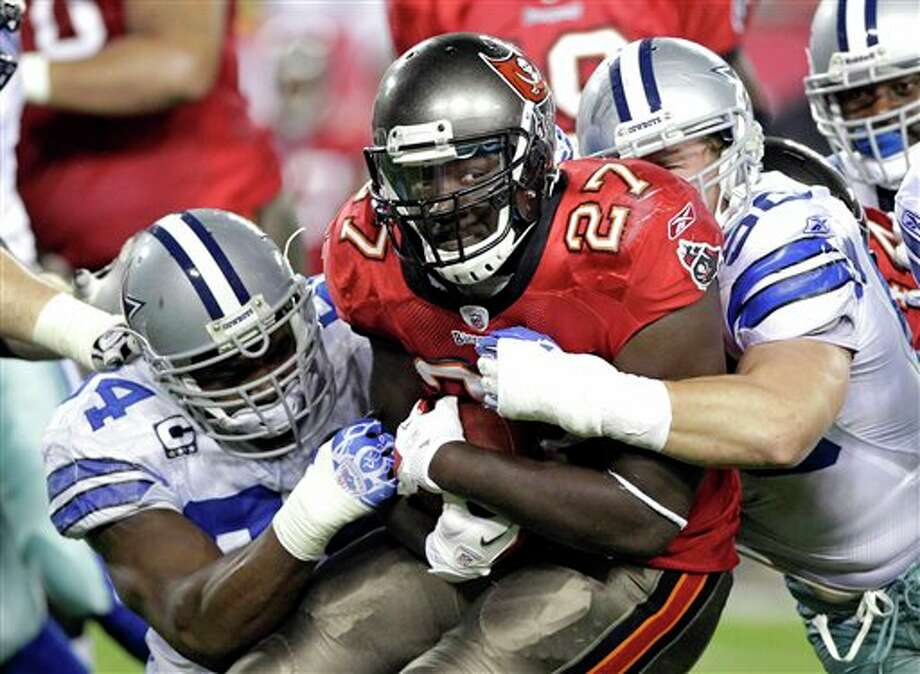 Tampa Bay Buccaneers running back LeGarrette Blount (27) is stopped after a short gain by Dallas Cowboys outside linebacker DeMarcus Ware, left, and inside linebacker Sean Lee during the first half of an NFL football game on Saturday, Dec. 17, 2011, in Tampa, Fla. (AP Photo/John Raoux) Photo: Associated Press