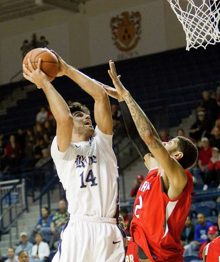 Rice's Arsalan Kazemi (14) shoots over Lamar's Nikko Acosta (2) during the first half of an NCAA basketball game between the Lamar Cardinals and the Rice Owls Saturday, December 17, 2011 in Houston. Lamar defeated Rice 87-81. Photo: Bob Levey, Houston Chronicle / ©2011 Bob Levey
