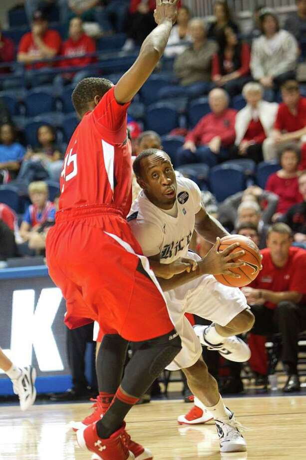 Rice's Tamir Jackson (3) looks for room to drive the baseline as Lamar's Stan Brown (35 defends during the first half of an NCAA basketball game between the Lamar Cardinals and the Rice Owls Saturday, December 17, 2011 in Houston. Lamar defeated Rice 87-81. Photo: Bob Levey, Houston Chronicle / ©2011 Bob Levey