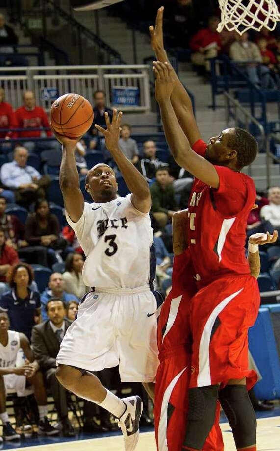 Rice's Tamir Jackson (3) hits a fade away shot  from the baseline as he is pressured by Lamar's Stan Brown (35) during the second half of an NCAA basketball game between the Lamar Cardinals and the Rice Owls Saturday, December 17, 2011 in Houston. Lamar defeated Rice 87-81. Photo: Bob Levey, Houston Chronicle / ©2011 Bob Levey