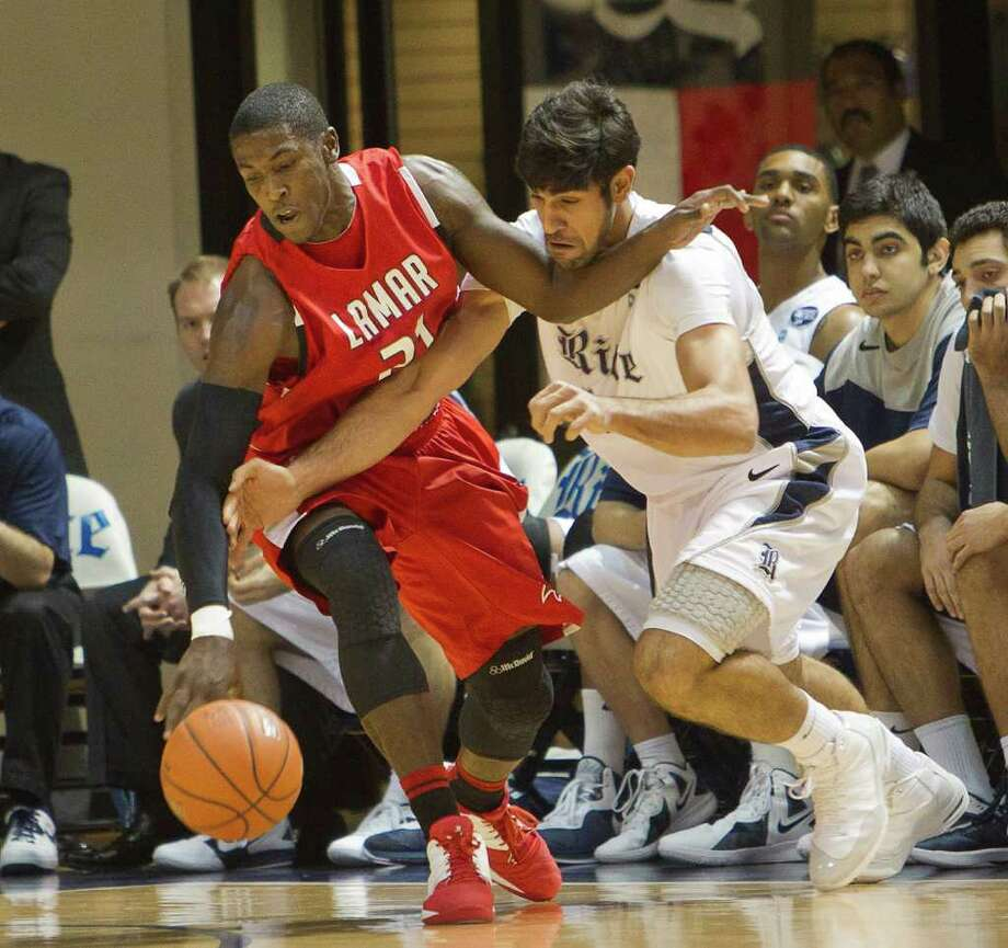 BOB LEVEY: FOR THE CHRONICLE WHO'S GOT IT?: Rice's Arsalan Kazemi (14) and Lamar's Nikko Acosta (21) battle for a loose ball in the first half. Photo: Bob Levey / ©2011 Bob Levey