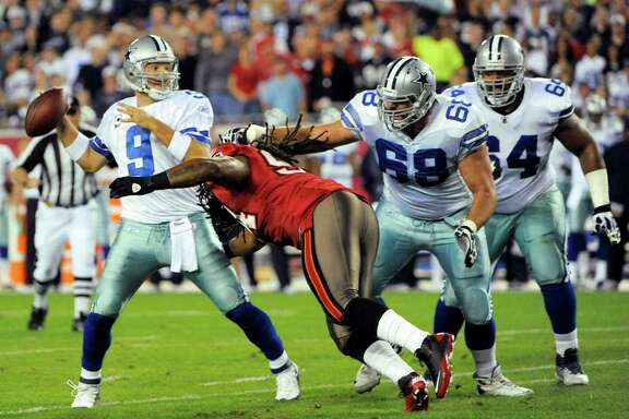 Dallas Cowboys quarterback Tony Romo (9) is hit by Tampa Bay Buccaneers defensive end Adrian Clayborn (94) as he throws an 8-yard touchdown pass to wide receiver Miles Austin during the first half of an NFL football game Saturday, Dec. 17, 2011, in Tampa, Fla. Defending for the Cowboys are offensive tackle Doug Free (68) and guard Montrae Holland (64). (AP Photo/Brian Blanco)