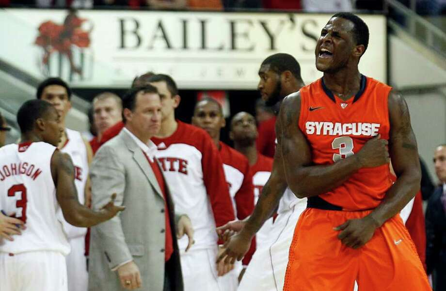 Syracuse's Dion Waiters (3) reacts as North Carolina State coach Mark Gottfried speaks with players during a timeout in the second half of an NCAA college basketball game in Raleigh, N.C., Saturday, Dec. 17, 2011. Syracuse won 88-72. (AP Photo/Gerry Broome) Photo: Gerry Broome