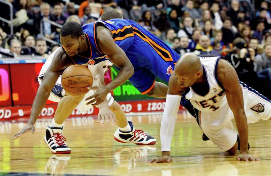 New York Knicks' Toney Douglas (23) dives for the ball past New Jersey Nets' Sundiata Gaines (1) during the first half of an NBA preseason basketball game in Newark, N.J., Saturday, Dec. 17, 2011. The Knicks won 92-83. (AP Photo/Mel Evans) Photo: Mel Evans
