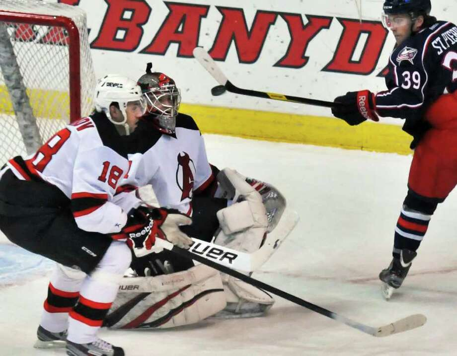 Albany Devils'  #18 Vladimir Zharkov, left, and goalie Jeff Frazee stop a shot by Springfield's #39 Martin St. Pierre in first period action at the Times Union Center in Albany Saturday Dec. 17, 2011.  (John Carl D'Annibale / Times Union) Photo: John Carl D'Annibale / 00015748C