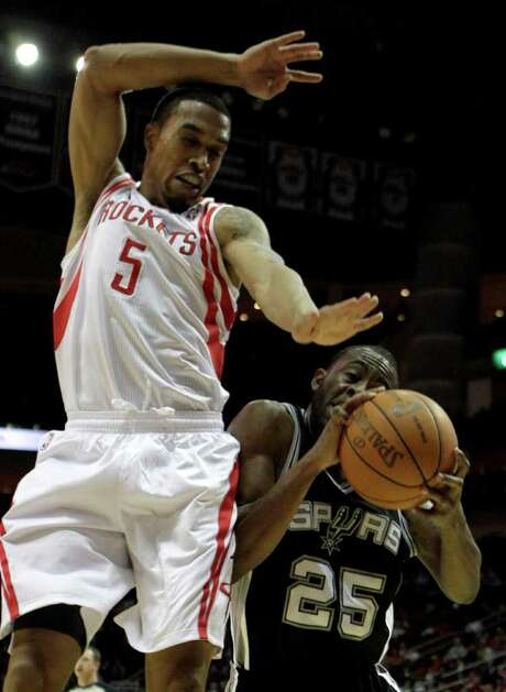 BRETT COOMER: CHRONICLE OOPS. IT'S EARLY: Rockets shooting guard Courtney Lee (5) gets faked off his feet by Spurs shooting guard James Anderson (25) and is called for a foul during the first half Saturday. Photo: Brett Coomer / © 2011 Houston Chronicle