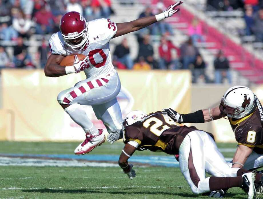 Temple running back Bernard Pierce (30) leaps over Wyoming defensive back Kenny Browder (24) and linebacker Brian Hendricks (8) in the second quarter of the New Mexico Bowl NCAA college football game in Albuquerque, N.M., Saturday, Dec. 17, 2011. (AP Photo/Jake Schoellkopf) Photo: Jake Schoellkopf