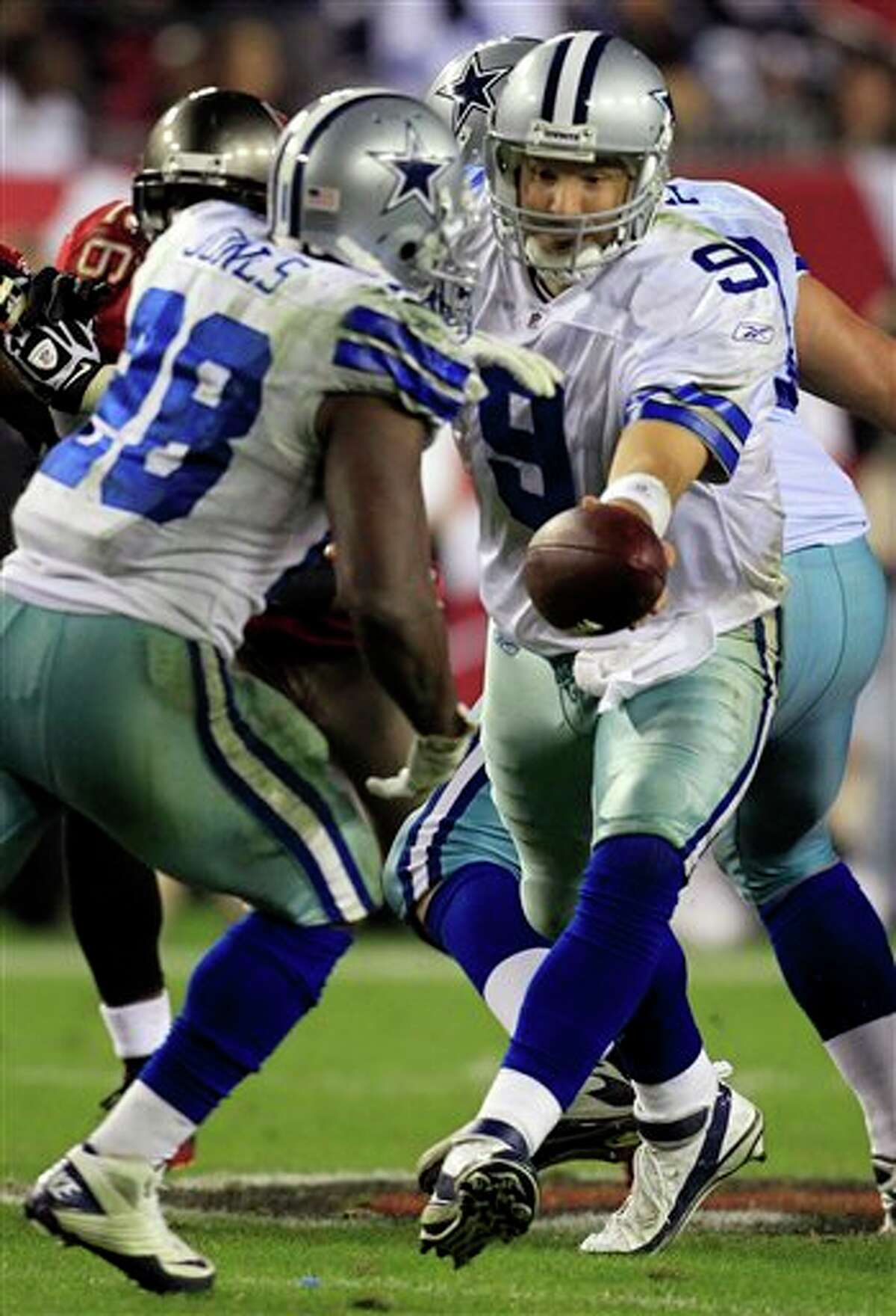 Dallas Cowboys quarterback Tony Romo (9) hands off to running back Felix Jones (28) during the second half of an NFL football game against the Tampa Bay Buccaneers Saturday, Dec. 17, 2011, in Tampa, Fla. (AP Photo/Chris O'Meara)