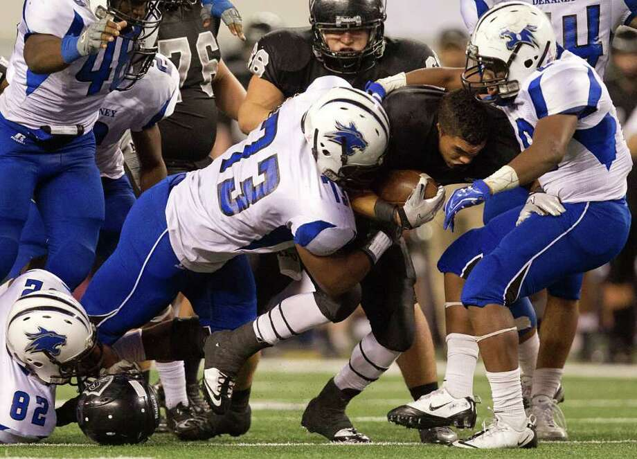 Cibolo Steele running back Justin Stockton loses his helmet as he is brought down by the Dekaney defense, including Immanuel Cassey (73) and Tyrell Kule (29),  during the second half of the 5A Div. 2 state championship high school football game at Cowboys Stadium on Saturday, Dec. 17, 2011, in Arlington.   Dekaney won the game 34-14. Photo: Smiley N. Pool, Houston Chronicle / © 2011  Houston Chronicle