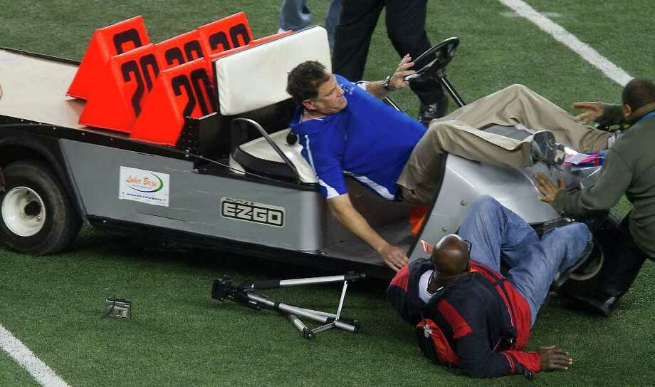 Spring Dekaney head coach Willie Amendola is upended as an out of control cart runs several bystanders over on the Cowboys Stadium field after Spring Dekaney defeated Cibolo Steele 34-14 during the Class 5A Divison II state championships high school football game on Saturday, Dec. 17, 2011, in Arlington, Texas. Two people were taken off the field by stretcher. (AP Photo/The Courier, Patric Schneider) Photo: Express-News