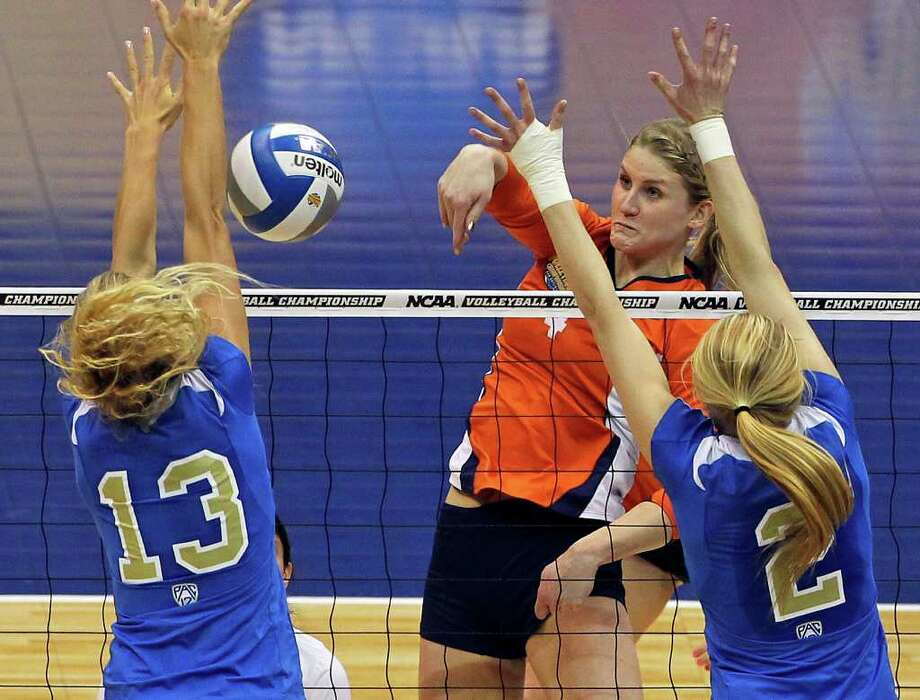 Colleen Ward hits into the defense of the Bruin's Zoe Nightingale and Kelly Reeves (2) as UCLA plays Illinois in the  2011 NCAA National Championship volleyball match at the Alamodome on December 17, 2011 Tom Reel/Staff Photo: TOM REEL, Express-News / © 2011 San Antonio Express-News