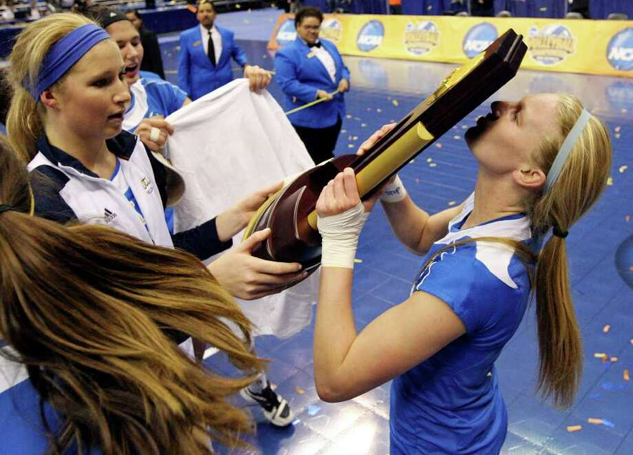 UCLA's Kelly Reeves kisses the trophy after the 2011 NCAA Division I Women's Volleyball National Championship match with Illinois Saturday Dec. 17, 2011 at the Alamodome. UCLA won 3-1. PHOTO BY EDWARD A. ORNELAS/eaornelas@express-news.net) Photo: EDWARD A. ORNELAS, Express-News / © SAN ANTONIO EXPRESS-NEWS (NFS)