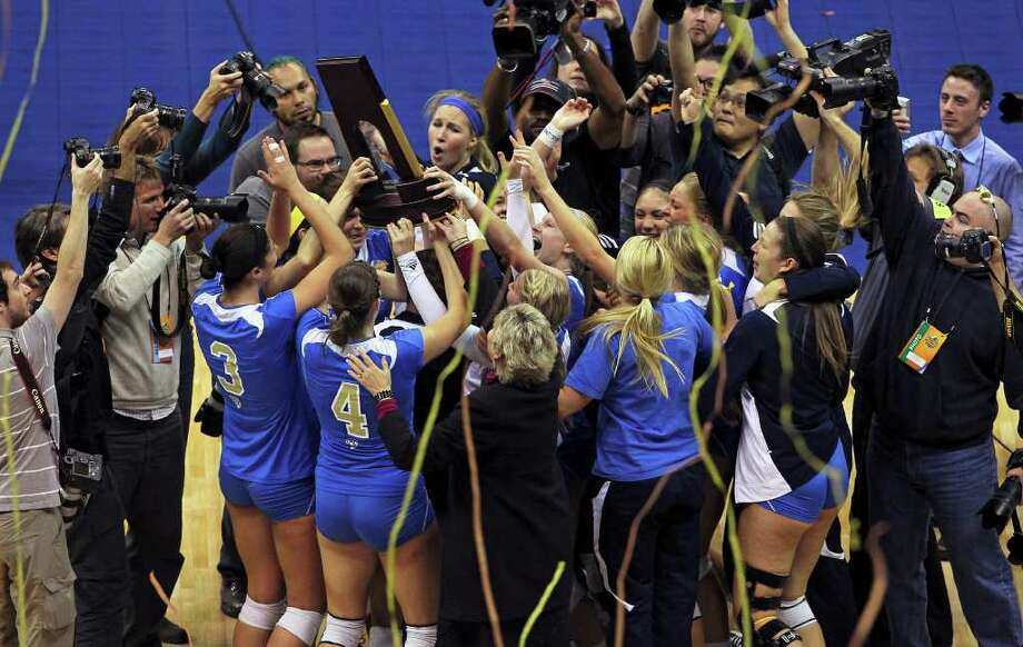 The Bruins celebrate with their trophy as UCLA beats Illinois 3-1 in the  2011 NCAA National Championship volleyball match at the Alamodome on December 17, 2011 Tom Reel/Staff Photo: TOM REEL, Express-News / © 2011 San Antonio Express-News