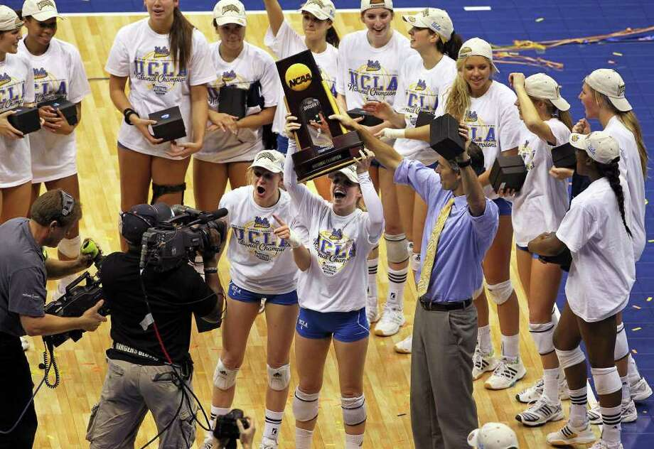 Lainey Gera hoists the trophy with teammates as UCLA beats Illinois in the  2011 NCAA National Championship volleyball match at the Alamodome on December 17, 2011 Tom Reel/Staff Photo: TOM REEL, Express-News / © 2011 San Antonio Express-News