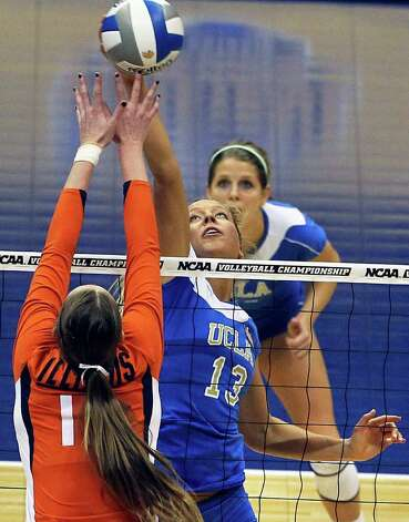 The Bruins' Zoe Nightingale moves the ball around Erin Johnson as  UCLA plays Illinois in the  2011 NCAA National Championship volleyball match at the Alamodome on December 17, 2011 Tom Reel/Staff Photo: TOM REEL, Express-News / © 2011 San Antonio Express-News