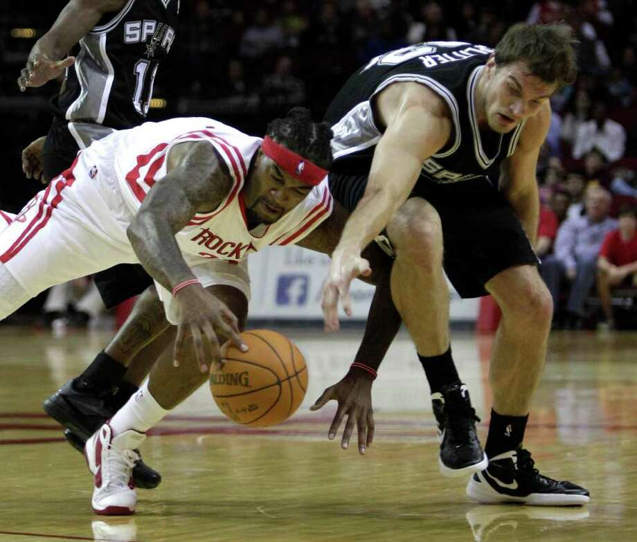 Houston Rockets forward Jordan Hill (27) and San Antonio Spurs forward Tiago Splitter (22) go after a loose ball during the first half of a pre-season NBA basketball game at Toyota Center Saturday, Dec. 17, 2011, in Houston. Photo: Brett Coomer, Houston Chronicle / © 2011 Houston Chronicle
