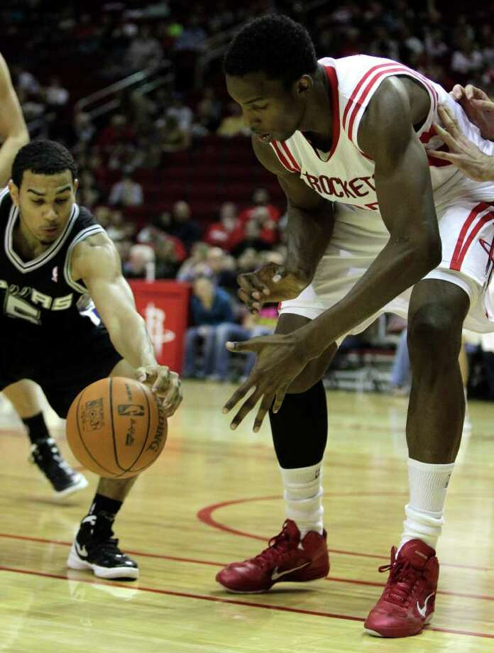 San Antonio Spurs guard Cory Joseph (5) comes up with a loose ball from Houston Rockets center Hasheem Thabeet (32) during the second half of a pre-season NBA basketball game at Toyota Center Saturday, Dec. 17, 2011, in Houston. The Rockets beat the Spurs 101-87. Photo: Brett Coomer, Houston Chronicle / © 2011 Houston Chronicle