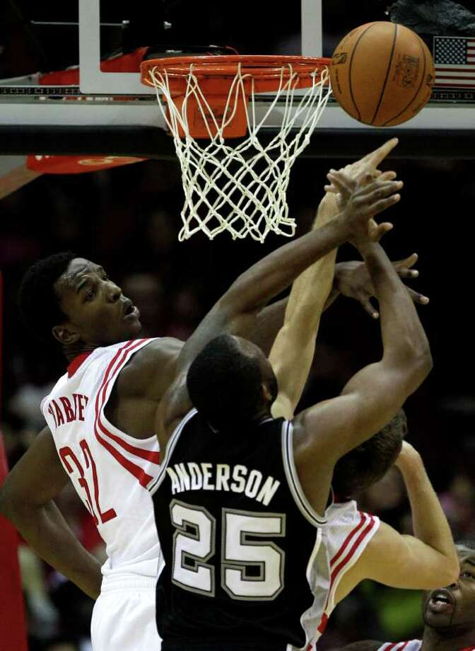 Houston Rockets center Hasheem Thabeet (32) defends a shot by San Antonio Spurs shooting guard James Anderson (25) during the second half of a pre-season NBA basketball game at Toyota Center Saturday, Dec. 17, 2011, in Houston. The Rockets beat the Spurs 101-87. Photo: Brett Coomer, Houston Chronicle / © 2011 Houston Chronicle