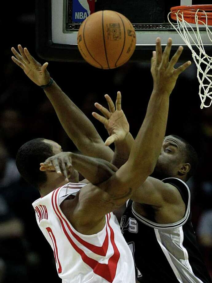 Houston Rockets forward Marcus Cousin (0) and San Antonio Spurs forward Gani Lawal (7) get tangled up as Cousin goes to the basket during the second half of a pre-season NBA basketball game at Toyota Center Saturday, Dec. 17, 2011, in Houston. The Rockets beat the Spurs 101-87. Photo: Brett Coomer, Houston Chronicle / © 2011 Houston Chronicle
