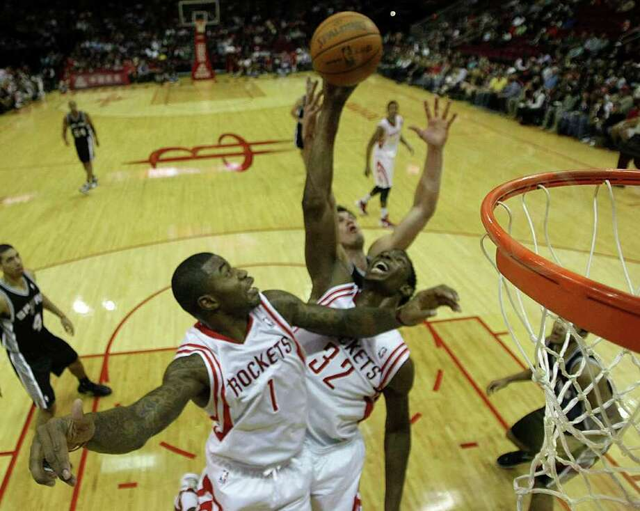 Houston Rockets small forward Terrence Williams (1) and Houston Rockets center Hasheem Thabeet (32) go after a rebound with San Antonio Spurs forward Tiago Splitter during the second half of a pre-season NBA basketball game at Toyota Center Saturday, Dec. 17, 2011, in Houston. The Rockets beat the Spurs 101-87. Photo: Brett Coomer, Houston Chronicle / © 2011 Houston Chronicle