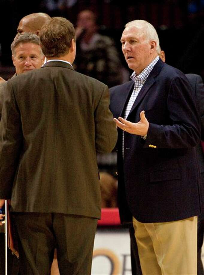 San Antonio Spurs head coach Gregg Popovich, right, talks with his staff during a time out in first quarter of a preseason NBA basketball game against the Houston Rockets, Saturday, Dec. 17, 2011, in Houston. (AP Photo/Dave Einsel) Photo: Associated Press