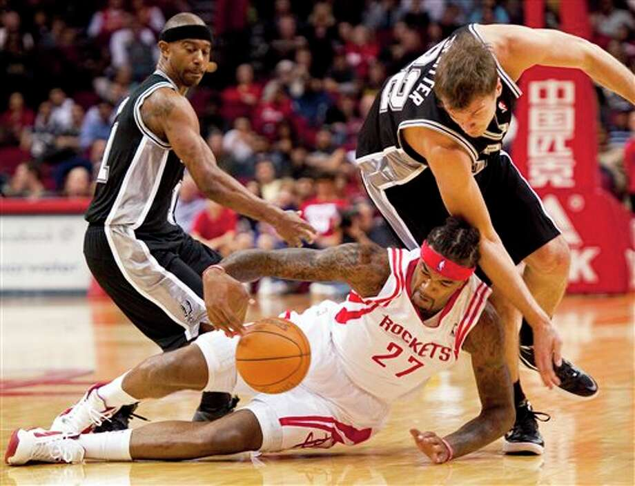 Houston Rockets' Jordan Hill (27) grabs a loose ball away from San Antonio Spurs' T.J. Ford, left, and Tiago Splitter, right, of Brazil, during the first quarter of a preseason NBA basketball game, Saturday, Dec. 17, 2011, in Houston. (AP Photo/Dave Einsel) Photo: Associated Press