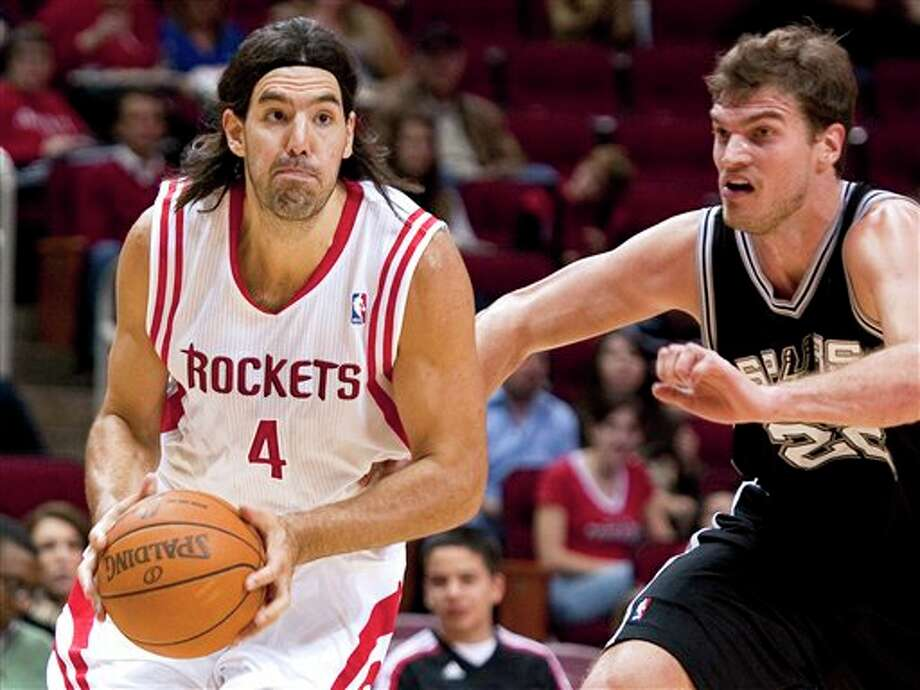 Houston Rockets' Luis Scola (4), of Argentina, drives around San Antonio Spurs' Tiago Splitter, right, of Brazil, during the first quarter of a preseason NBA basketball game, Saturday, Dec. 17, 2011, in Houston. (AP Photo/Dave Einsel) Photo: Associated Press