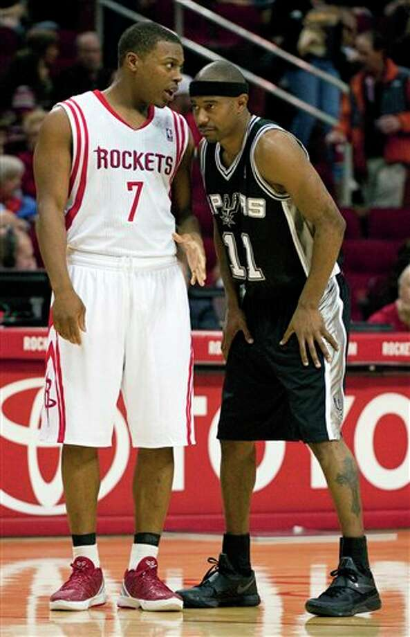 Houston Rockets' Kyle Lowry (7) talks with San Antonio Spurs' T.J. Ford (11) during the third quarter of a preseason NBA basketball game, Saturday, Dec. 17, 2011, in Houston. The Rockets defeated the Spurs 101-87. (AP Photo/Dave Einsel) Photo: Associated Press