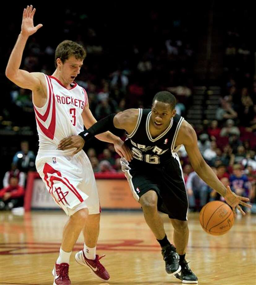 San Antonio Spurs' Antoine Hood (26) drives around Houston Rockets' Goran Dragic (3), of Slovenia, during the fourth quarter of a preseason NBA basketball game, Saturday, Dec. 17, 2011, in Houston. The Rockets defeated the Spurs 101-87. (AP Photo/Dave Einsel) Photo: Associated Press