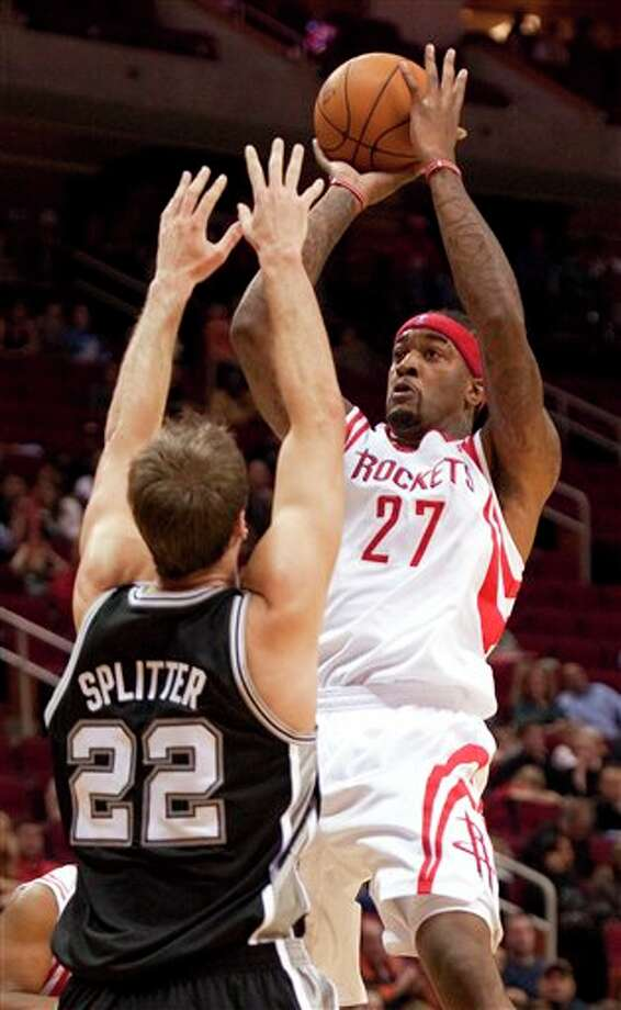 Houston Rockets' Jordan Hill (27) shoots over San Antonio Spurs' Tiago Splitter (22) during the first quarter of a preseason NBA basketball game, Saturday, Dec. 17, 2011, in Houston. The Rockets defeated the Spurs 101-87. (AP Photo/Dave Einsel) Photo: Associated Press