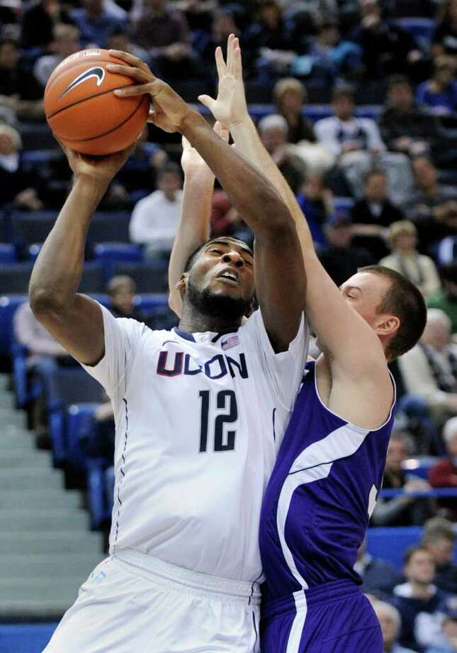 Connecticut's Andre Drummond (12) is fouled by Holy Cross' Jordan Stevens during the second half of an NCAA college basketball game in Hartford, Conn., on Sunday, Dec. 18, 2011. Drummond scored a game-high 24 points in his team's 77-40 victory. (AP Photo/Fred Beckham) Photo: Fred Beckham, AP / FR153656 AP