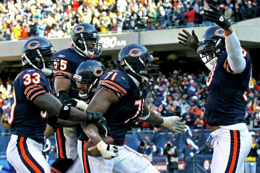 Chicago Bears defensive end Israel Idonije (71) celebrates with teammates Julius Peppers, right, Cha