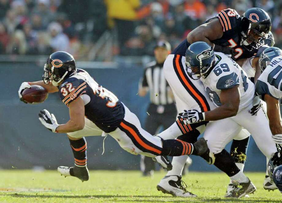 Chicago Bears running back Kahlil Bell (32) picks up yardage as offensive tackle J'Marcus Webb (73) blocks Seattle Seahawks defensive tackle Clinton McDonald (69) in the first half of an NFL football game in Chicago, Sunday, Dec. 18, 2011. Photo: AP