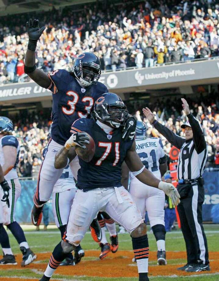 Chicago Bears defensive end Israel Idonije (71) celebrates with teammate Charles Tillman (33) after scoring on a fumble recovery in the end zone in the first half of an NFL football game against the Seattle Seahawks in Chicago, Sunday, Dec. 18, 2011. Photo: AP