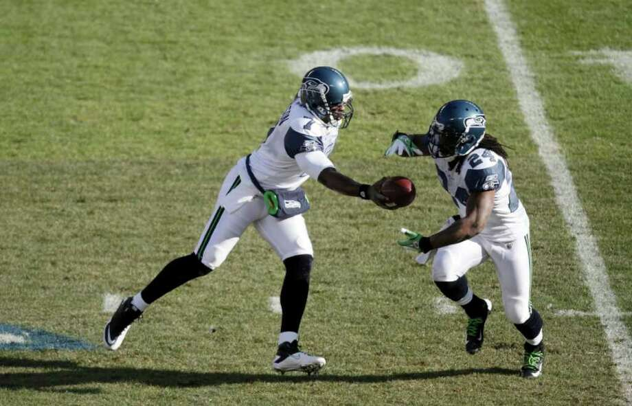 Seattle Seahawks quarterback Tarvaris Jackson (7) hands the ball off to running back Marshawn Lynch (24) in the first half of an NFL football game in Chicago, Sunday, Dec. 18, 2011. Photo: AP