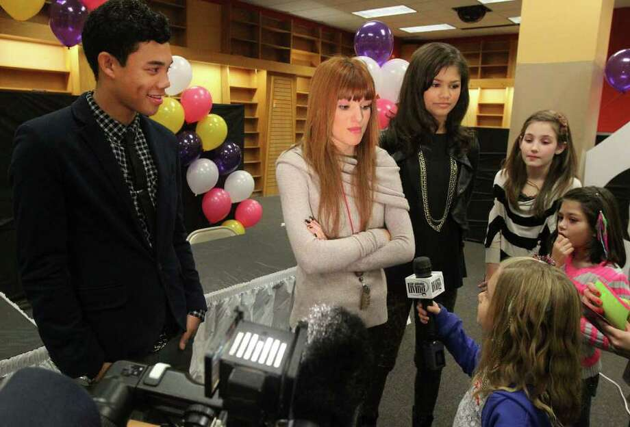 "Addie Dickson,7, (bottom, right, holding microphone) interviews ""Shake it Up"" star Bella Thorne, a.k.a. ""CeCe Jones"" (center, arms folded) during an appearance Sunday December 18, 2011 at the Alamo Quarry Market. On the left is Roshon Fegan who plays ""Ty"" on the show and on the right is Zendaya (in black, wearing necklace) who plays ""Rocky Blue."" On the far right are Madeleine Manlove,13, (in black and white stripes) and Kylie Elam,8, (pink stripes, hand on mouth). ""Shake it Up"" is a Disney production about young dancers and performers. JOHN DAVENPORT/jdavenport@express-news.net Photo: SAN ANTONIO EXPRESS-NEWS"