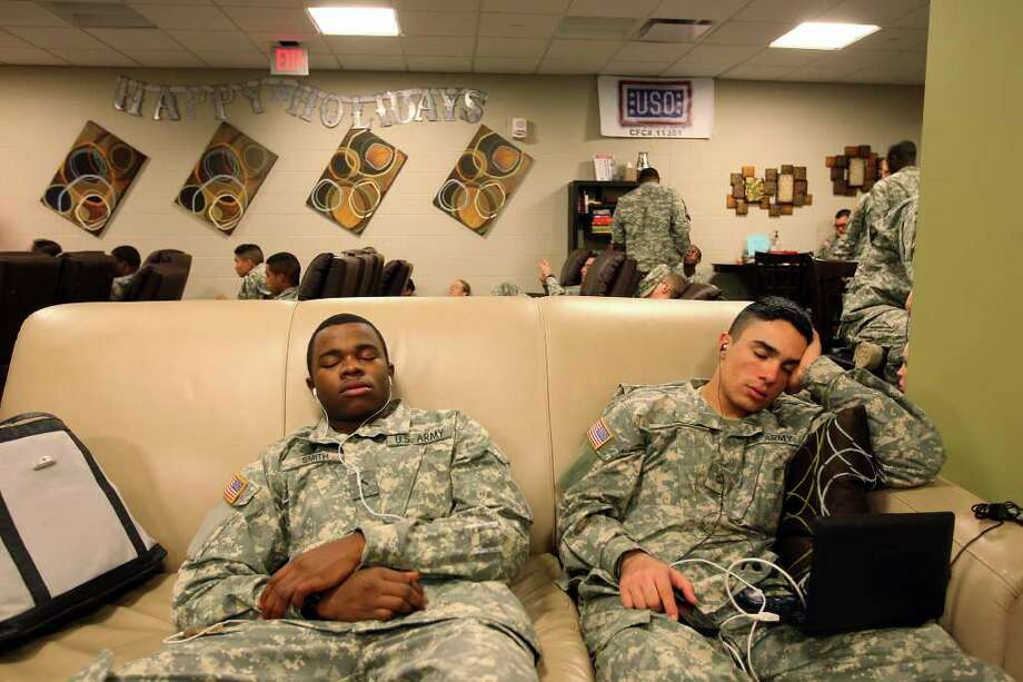 METRO -- U.S. Army Pvt. Malcolm Smith, 19, of Clarksville, Tennessee, left, and Pfc. Christopher Fine, 20, of Las Vegas, Nevada, take a break as they wait for the fllight at the USO in the San Antonio International Airport, Sunday, Dec. 18, 2011. The and other members of the U.S. Military stationed in San Antonio are on an extended leave for the Christmas holidays. JERRY LARA/glara@express-news.net Photo: JERRY LARA, San Antonio Express-News / SAN ANTONIO EXPRESS-NEWS